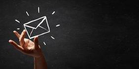 Hand und Symbol Briefumschalg vor schwarzem Hintergrund