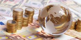 Geld und kleine Weltkugel aus Glas