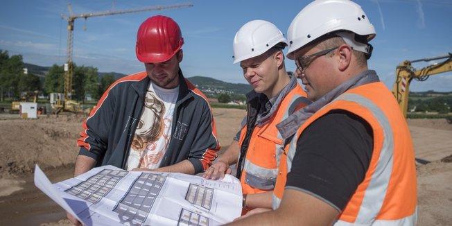 Straßenbauer mit Plänen auf der Baustelle
