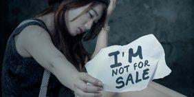 """Sitzende Frau, die Kopf auf eine Hand stützt, verzweifelter Gesichtsausdruck, die zweite Hand hält ein Schild in die Kamera mit der Aufschrift """"I am not for sale"""""""