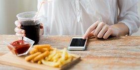 Pommes mit Getränk und Mobiltelefon