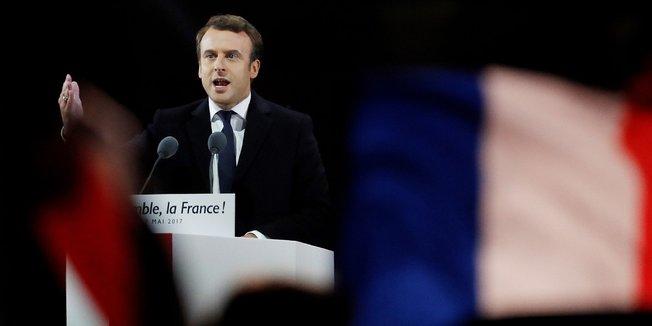 Emmanuel Macron bei einer Rede im Mai 2017 (Hintergrund schwarz, Vordergrund: französische Fahnen)