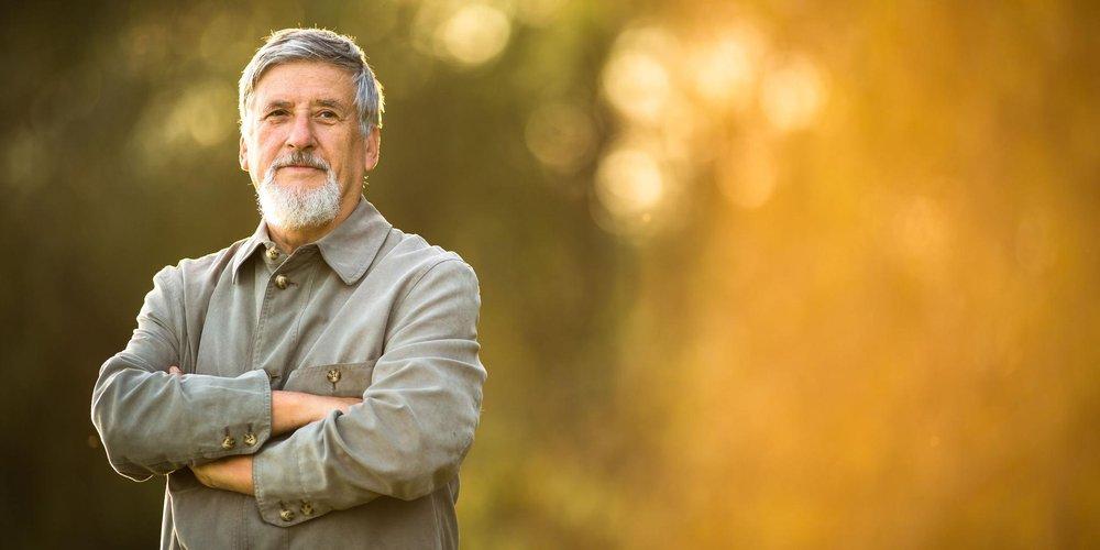 Zufriedener grauhaariger Mann im Sonnenlicht