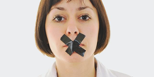 Frau mit Kreuz aus Klebeband über dem Mund - Symbol für fehlende Meinungsfreiheit