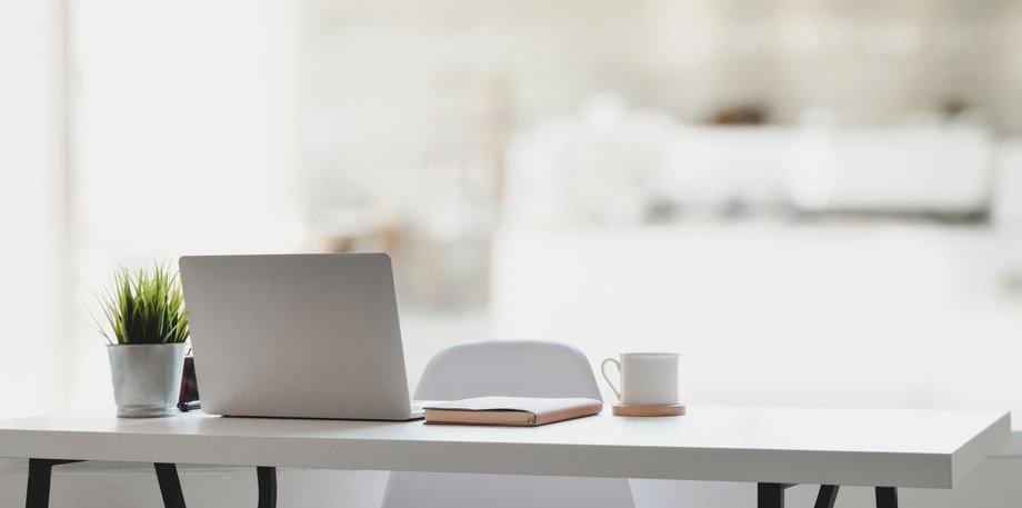 Weißer Tisch mit Laptop, Notizbuch, Kaffeetasse und Topfpflanze