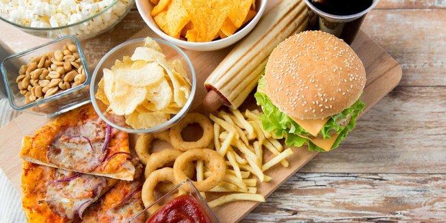 Diverses Fast-Food wie Burger und Pizza auf einem Holztablett