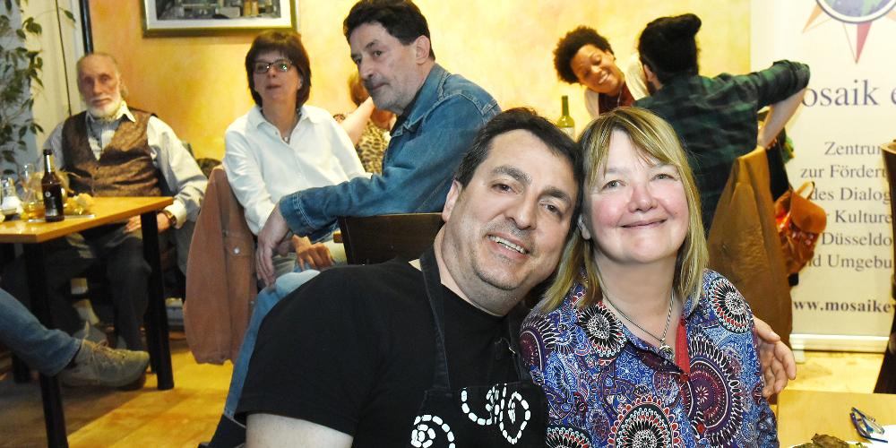 Ein Mann und eine Frau blicken in einem Restaurant sitzend lachend in die Kamera