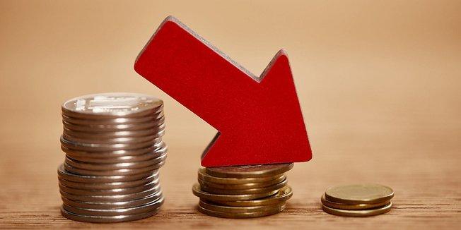 Tendenz: roter Pfeil auf Münzen platziert zeigt nach unten