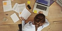 Frau mit Papieren und Laptop an einem Holztisch