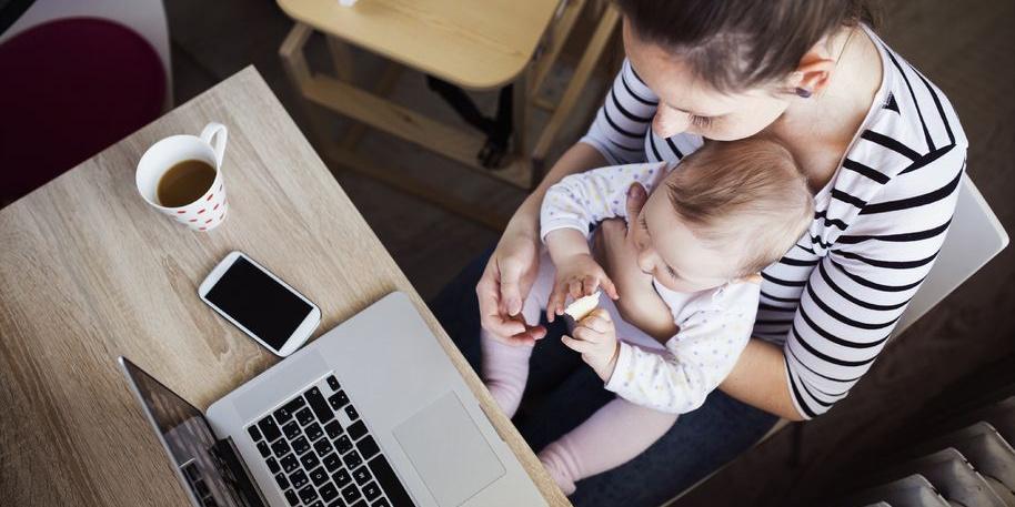 Junge Frau mit Baby auf dem Schoß am Schreibtisch