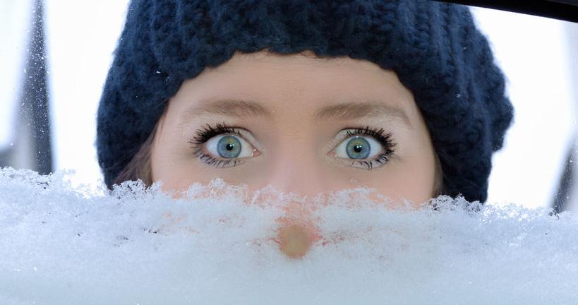 Frau mit Mütze schaut in zugeschneites Autofenster