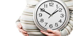Bauch einer Schwangeren Frau mit runder Wanduhr