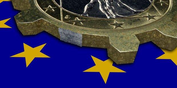 Euro Münze in Form eines Zahnrads auf EU-Flagge