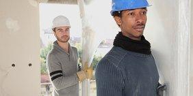 Zwei Handwerker tragen ein Bauteil
