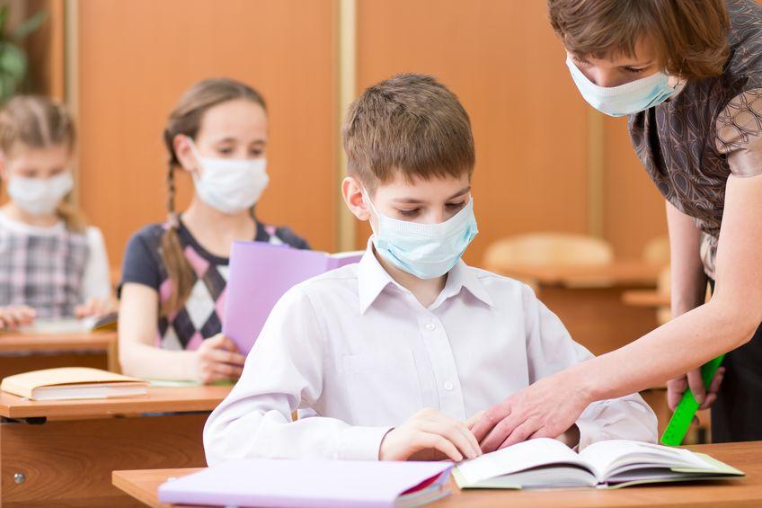 Kinder und Lehrerin mit Mund-Nasen-Schutz in der Schule