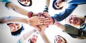 Junge Menschen Frauen und Männer bilden eine Kreis und halten sich an den Hängen