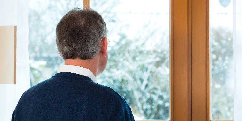 Älterer Mann blickt aus Fenster