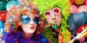 Mann und Frau mit bunten Perücken und Partyartikeln verkleidet vor Kulisse mit Luftballons