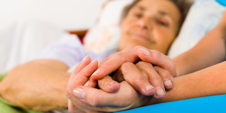 Pflegende Angehörige hält Hand am Bett