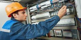 Elektriker mit Bauhelm an Schaltschrank