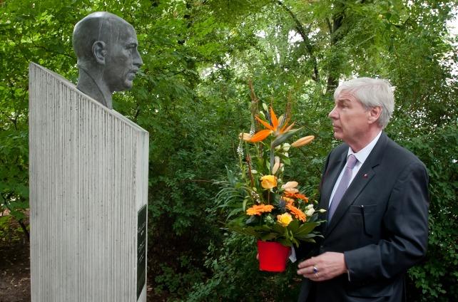 Michael Sommer mit Blumen vor der restaurierte Büste von Wilhelm Leuschner