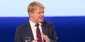 DGB-Vorsitzender Reiner Hoffmann bei einer Talkrunde mit Mikrofon