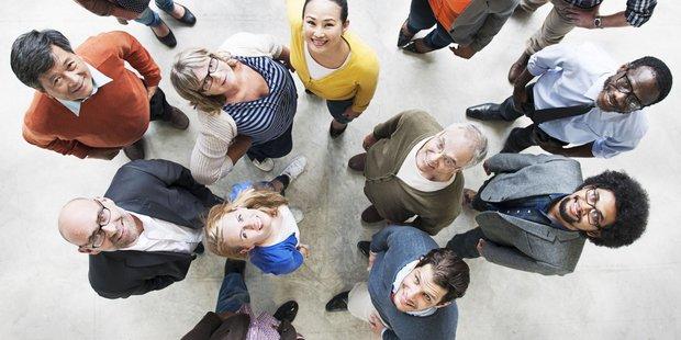 Ansammlung diverser Menschen verschiedenem Geschlechts und Herkunft werden schauen nach ob in die Kamera
