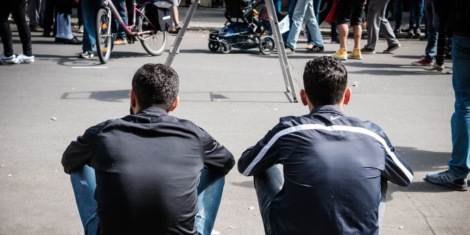 Zwei Männer in öhnlichem Outfit sitzen auf der Stufe in einer Fußgängerzone, Rückenansicht