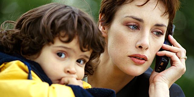Frau mit Handy, daneben ein gelangweiltes Kind