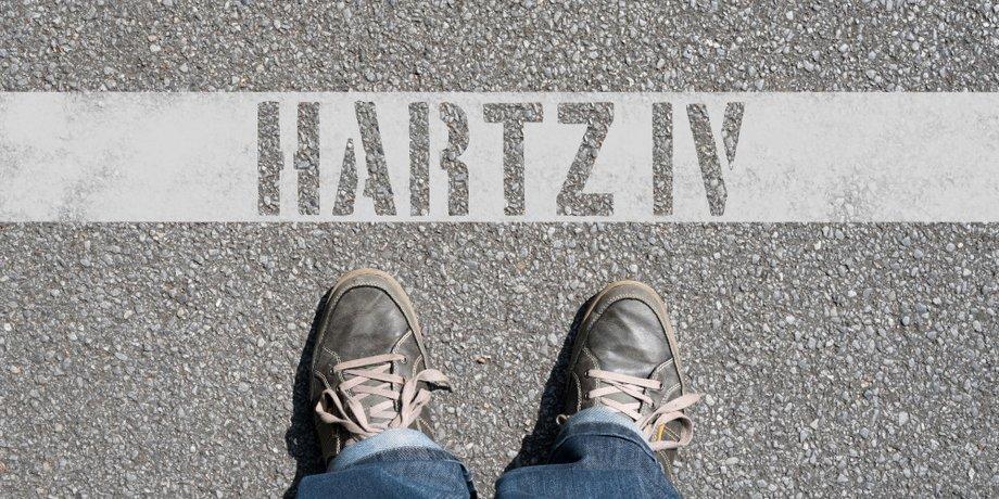 """Schuhe stehen auf Asphalt vor Schriftzug """"Hartz IV"""""""