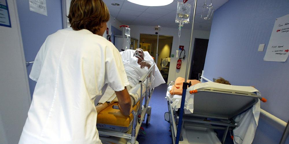 Pflegerin schiebt Bett mit Patient durch Krankenhausflur