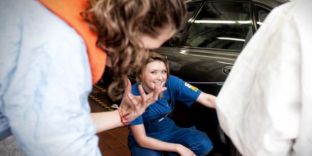 """Junge Frau in """"Blaumann"""" neben Auto in Kfz-Werkstatt"""