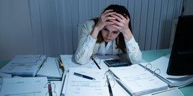 Junge Frau sitzt an überfülltem Schreibtisch und stützt den Kopf auf die Hände