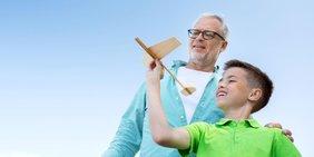 Großvater und Enkel mit Spielzeug-Flugzeug vor blauem Himmel