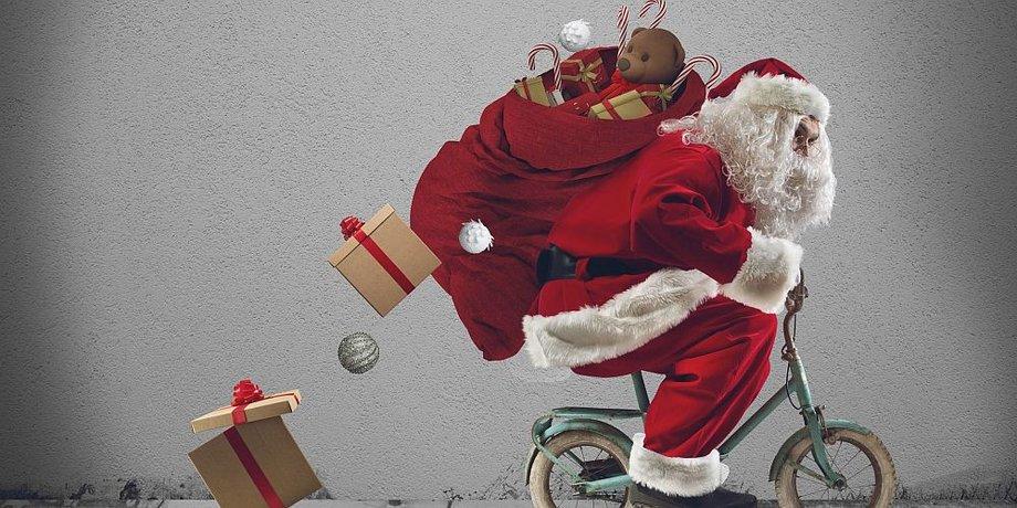 Weihnachtsmann liefert auf kleinem Fahrrad Geschenke aus