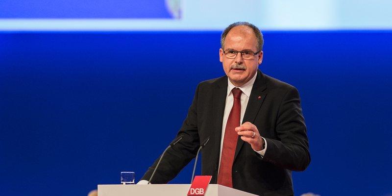 DGB-Vorstandsmitglied Stefan Körzell bei Rede an Rednerpult mit DGB-Logo, blauer Hintergrund