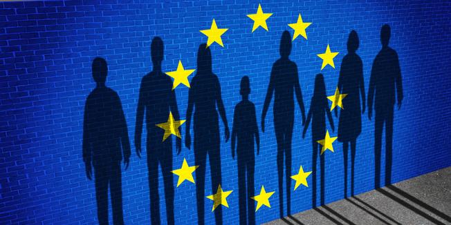 Europäische Flagge auf einer Mauer mit Schatten einer Menschenkette