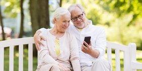 Älteres Paar mit Smartphone auf Parkbank