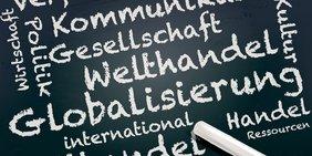 """Mit Kreide geschriebene Wörter, unter anderem """"Globalisierung"""", """"Welthandel"""", """"international"""""""