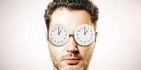 Mann mit zwei Uhren vor den Augen