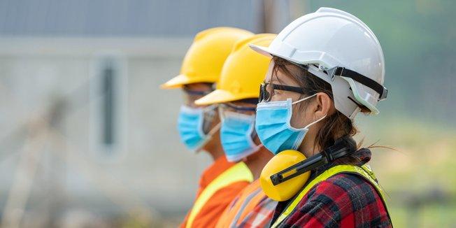 Drei Bauarbeiter*innen / Handwerker*innen mit Schutzhelm und Mund-Nasen-Schutz; blicken mit verschränkten Armen nach links