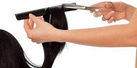 Hand schneidet Haare mit Kamm und Scheere