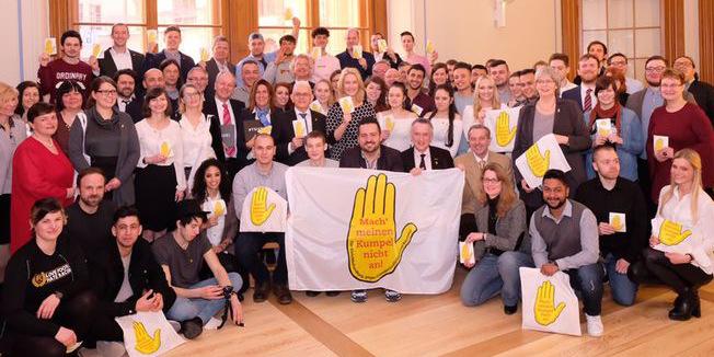 """Personengruppe in großem Saal, Blick in Kamera, Transparente und Schilder mit dem Logo einer """"Gelben Hand"""""""