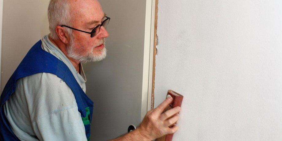 Älterer Mann beim Ausputzen einer Wand