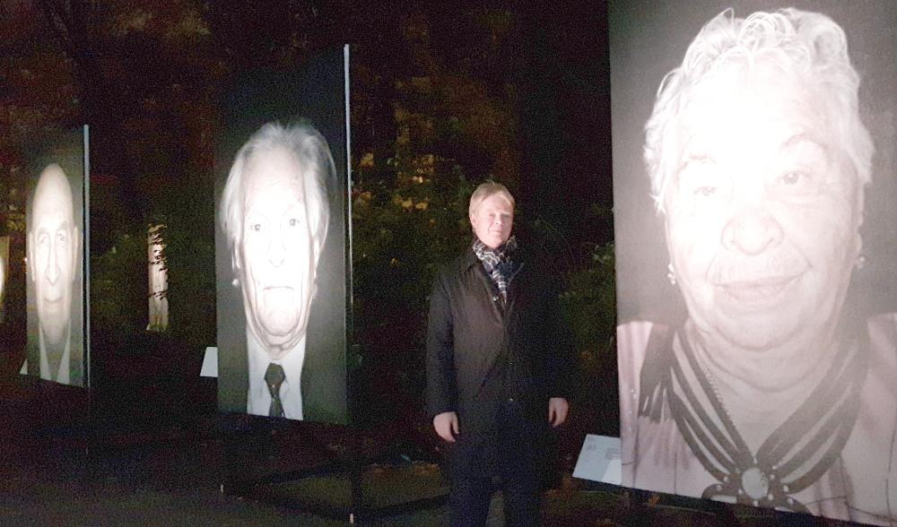 """Reiner Hoffmann zwischen den Porträts der Ausstellung """"Gegen das Vergessen"""""""
