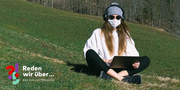 Home Office in Cornoa-Zeiten: Frau arbeitet mit Gesichtsmaske auf einer Wiese