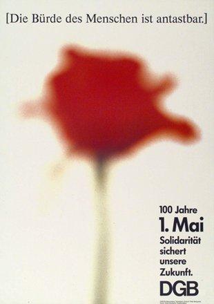 Plakat 1. Mai 1990: Text: 100 Jahre 1. Mai. Solidarität sichert unsere Zukunft. DGB. Motiv: Im Hintergrund eine rote Nelke, mittig und unscharf auf beigen Grund.