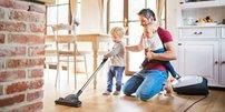 Vater mit zwei kleinen Kindern, staubsaugen gemeinsam den Küchenboden