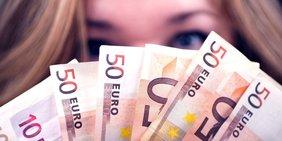 Frau hält Geldscheine vor das Gesicht