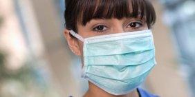 Nahaufnahme von Frau mit Mund-Nasen-Schutz (und blauer Pflegepersonalkleidung)